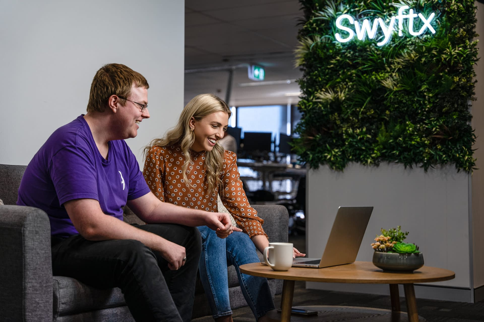 Man and woman looking at computer in office